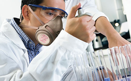 technician working in laboratory wearing ear and eye protection